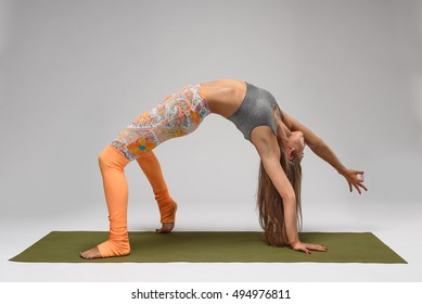 Girl standing in camatkarasana pose on gray background. Studio