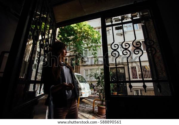 girl standing in the doorway to the street. Krasivayavintazhnaya bars on the windows. View of the lovely narrow street.