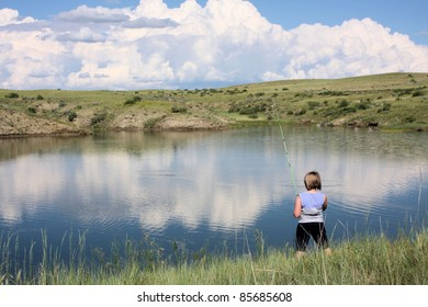 Girl standing at the edge of a pond fishing.