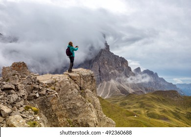 girl standing at the edge of rock and taking a photo on a smartphone. Dolomites, Italy.