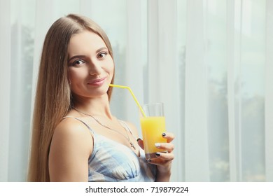 The girl is standing with freshly squeezed juice in front of the window.