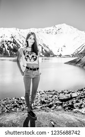"""Girl standing in front of the amazing mountain views of the waters from the """"Embalse del Yeso"""" (Cast Lake) close to Santiago de Chile city in Andes mountains. Snow mountains and water reflections"""