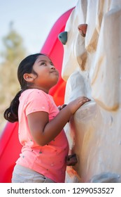 Girl standing in front of a climbing wall looking up with a thoughful expression on face.