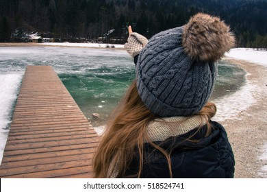 Girl standing in front of a frozen lake with a wooden pier pointing towards the sky