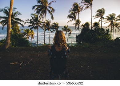 Girl standing in front of palm trees and the ocean at sunset