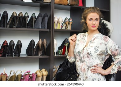 Girl standing in front of shoes in her shoe closet or a shoe store.