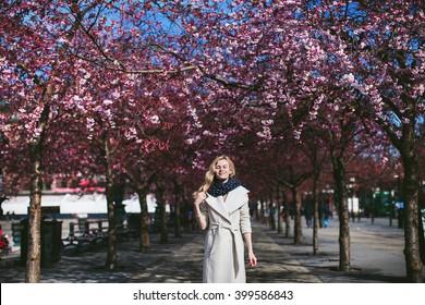 girl standing in the garden of flowering trees