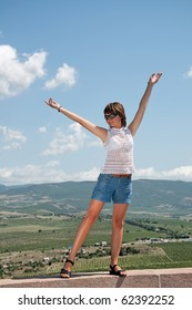 girl is standing with hands up against the background of beautiful scenery