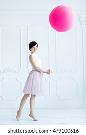 girl standing and holding a big pink balloon Cute girl playing with a pink balloon