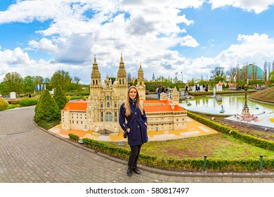 Girl standing in the Mini Europe park in Brussels next to a Catlonia Spanish cathedral.