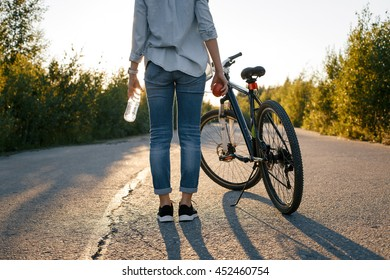 girl standing next to the bike back on the road in the summer