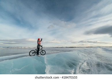 Girl standing on a bmx on the beautiful and dangerous ice and looks into the distance.