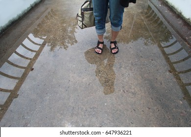girl standing on a bridge. Creative photo of rain mood. Woman's reflection on a wet pavement after the rain. The legs of a woman, the reflection tourist on a wet bridge after the rain.