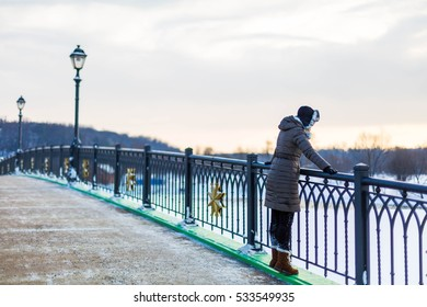 A girl standing on the bridge and looking down.