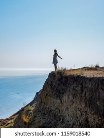 The girl is standing on a cliff near the sea.