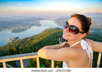 Girl standing on deck of Pyramidenkogel viewing tower in Carinthia. Tourist spot. View at lake and Klagenfurt city
