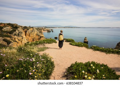 Girl standing on the edge of a cliff in Lagos, Algarve