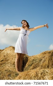 Girl  standing on hay with blue sky in background