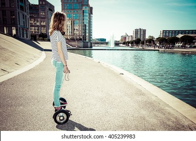 a girl standing on his profile hoverboard in a modern urban landscape waterfront