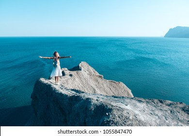 Girl standing on the mountain top over blue sea view