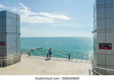 The girl is standing on the observation deck with a view of the sea, the Adler railway station, the inscription on the signs-exit, buses. Adler, Sochi -Russia