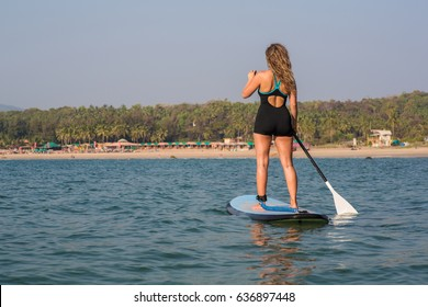 Girl standing on a paddle board in the sea in front of a beach.
