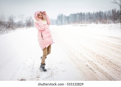 girl standing on the road in winter. snowing. girl smiling. I rejoice in the winter. blizzard. in pink down jacket. white scarf