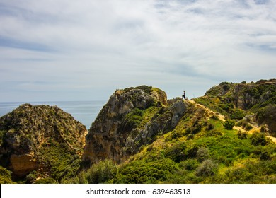 Girl standing on a rock overlooking Lagos, Algarve beaches from a cliff
