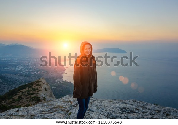 girl standing on a rock in the rays of the rising sun, a journey