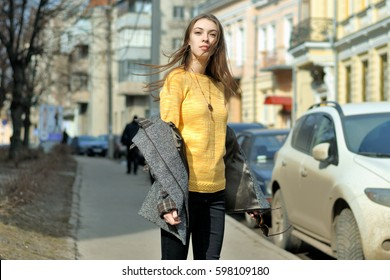 Girl is standing on the sidewalk near parked cars. The wind waved her hair, she took off her gray coat and remained stiff in the yellow sweater.