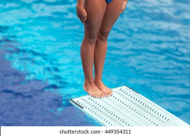 Girl standing on a springboard, preparing to dive