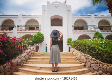 girl is standing on the steps in front of the big house