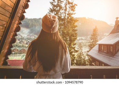 The girl is standing on a terraced house in a mountainous area. In good winter weather.