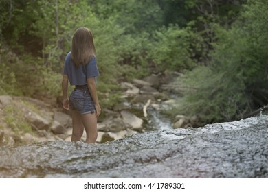 Girl standing on a waterfall looking into the distance
