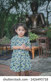 girl standing and paying respect to the Buddha