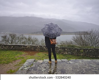 Girl standing in rain under her umbrella watching mountain lake view. Autumn concept.