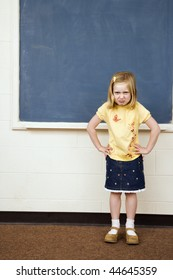 Girl standing in school classroom with hands on hips and pouty facial expression. Vertically framed shot.