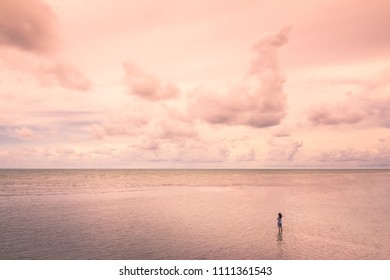 Girl standing in the sea in a lonely atmosphere.