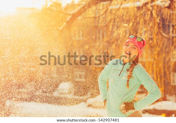 Girl standing in snow. Young woman having fun in winter park. Health nature relax fashion fitness concept.