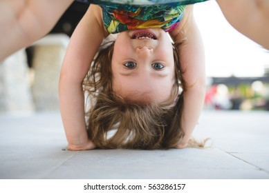 girl standing upside down and laughing