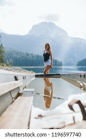 girl standing in white shorts, against a background of mountains and a black lake in the reflection of a broken boat