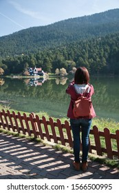A girl stands alone on a pier on a forest lake in gloomy weather in late autumn.