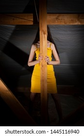 The girl stands behind a wooden stick in a yellow dress. Art photography in the style of geometry.