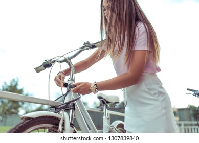 A girl stands with bicycle in summer in city. In hands of a lock with a code, it closes and protects its transport against theft. The concept of protection against theft and thieves of bicycles.
