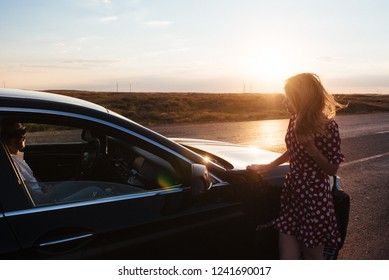 A girl stands by the car on the road
