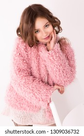 A girl stands leaning on a chair, looking at the camera and smiling. A child in a pink spring coat. Children's fashion.
