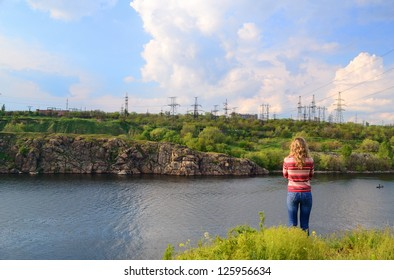 The girl stands near the river and looks at a power line
