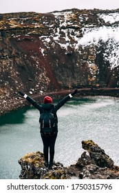 A girl stands on a cliff above Lake Kerid - a crater volcanic lake in Iceland. Red volcanic soil, similar to Martian landscapes. Hands thrown up over his head and rejoices.