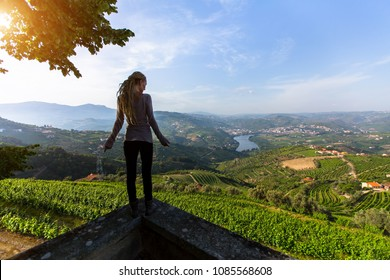 Girl stands on a cliff overlooking of river, vineyards are on a hills Douro Valley, Portugal.