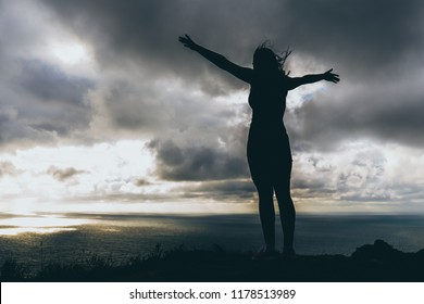 the girl stands on the edge of a high mountain to the wind blew her hair and body